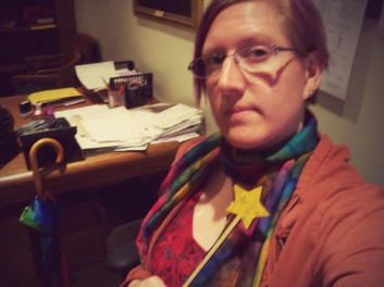 A bisexual as seen in the wild, with fairy wand and rainbow scarf, which I wore to my grandmother's funeral because Grandma always loved a spot of color.